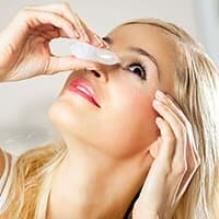 Young woman putting eyedrops in eyes