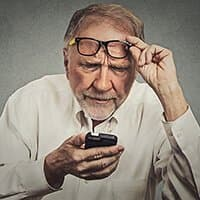 Older man struggling to see phone screen